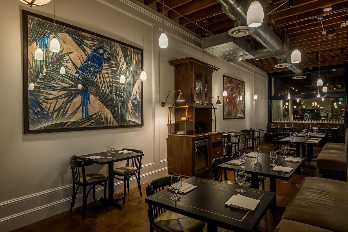 A dim dining room with flourishing artwork.