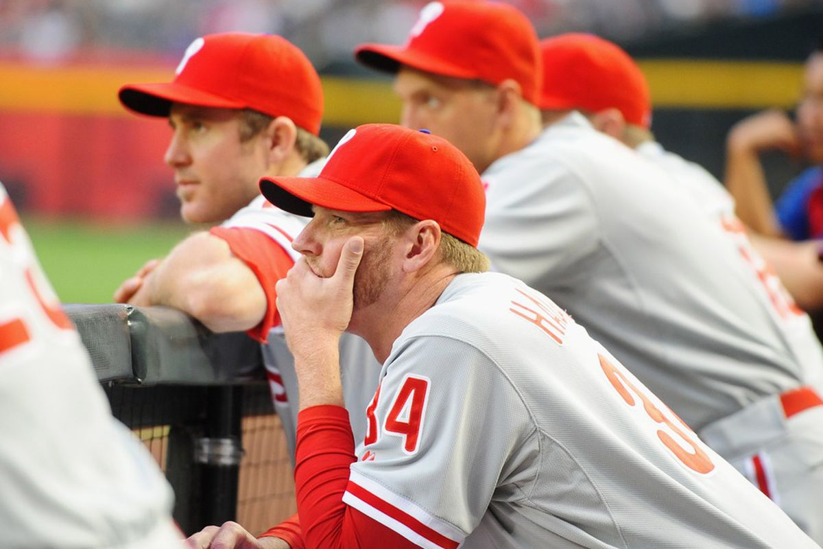 Apr. 23, 2012; Phoenix, AZ, USA; Philadelphia Phillies pitcher Roy Halladay (center) watches from the bench alongside Chase Utley in the first inning against the Arizona Diamondbacks at Chase Field. Mandatory Credit: Mark J. Rebilas-US PRESSWIRE