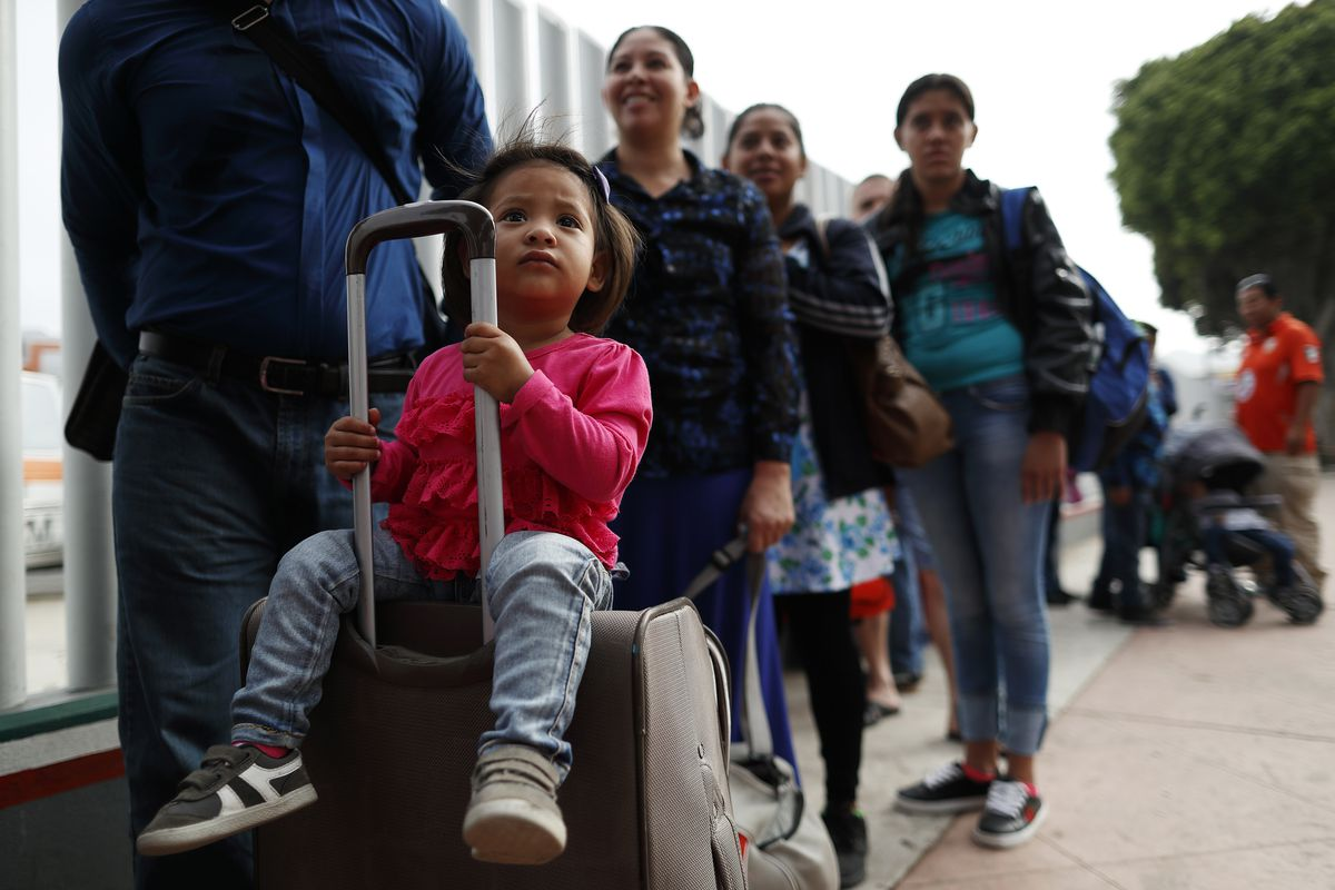 FILE - Merari Calderon, of El Salvador, lines up with her father, Alexander Calderon, left, to cross into the U.S. to begin the process of applying for asylum Thursday, July 26, 2018, near the San Ysidro port of entry in Tijuana, Mexico.