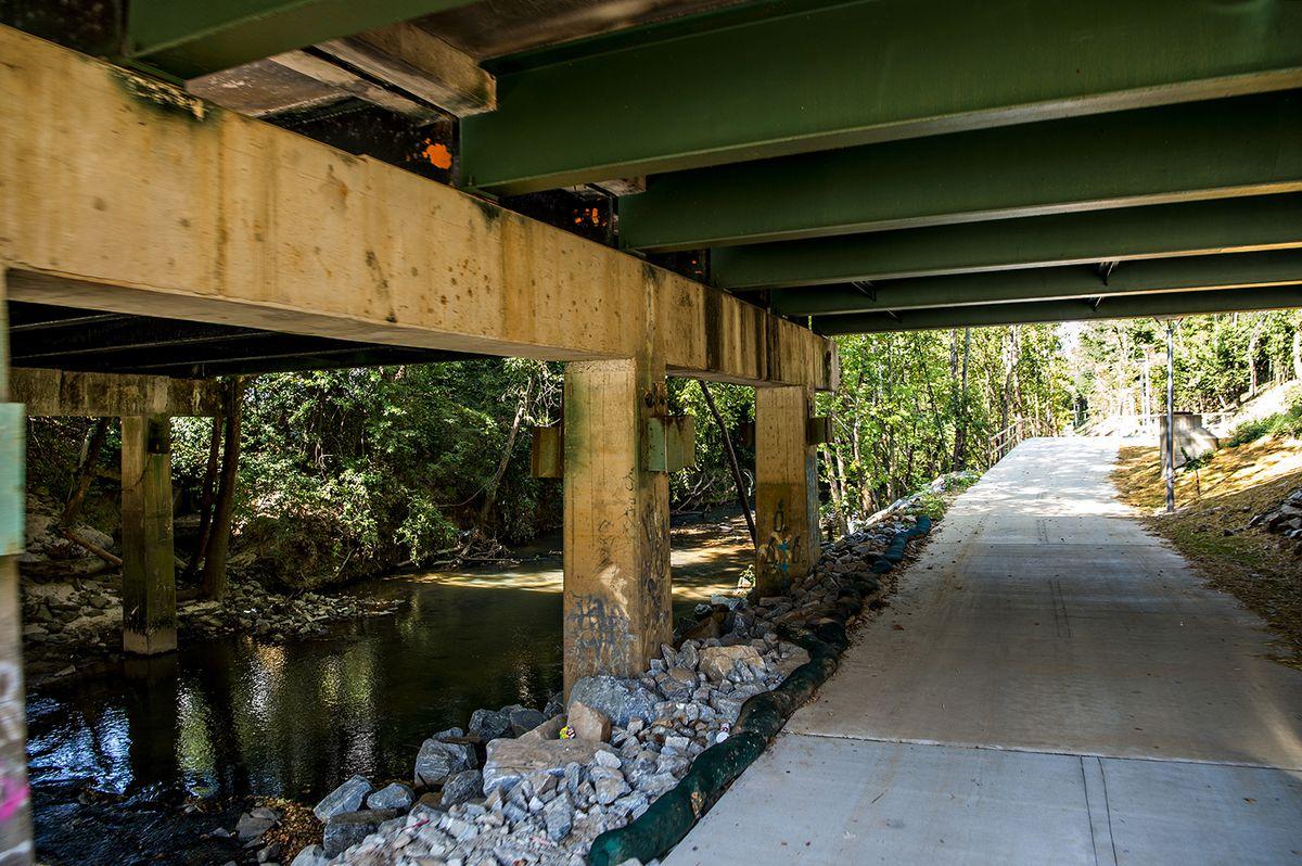 A trail beneath a green bridge.