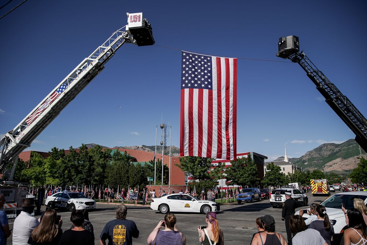 Onlookers watch as a procession of law enforcement officers escorts the body of fallen Ogden police officer Nathan Lyday past the Francom Public Safety Center in Ogden on Friday, May 29, 2020. Lyday was shot and killed Thursday while responding to a domestic violence call.