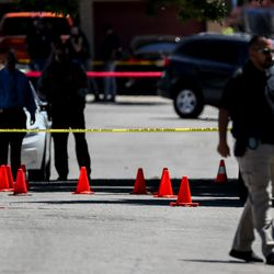 Orange cones dot the street as law enforcement officers continue to investigate an officer-involved shooting on Jackson Avenue in Ogden on Thursday, May 28, 2020.
