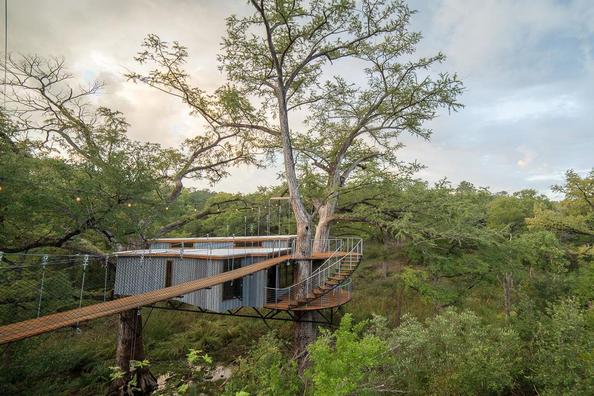 A photo of a flat-roofed, metal-sized structure built into two trees over a shallow ravine. A suspended walkway leads to the house, and a curved stairway leads from there to a bottom deck and entrance.