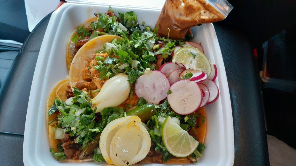 A pile of tacos with whole grilled onions from Spanglish in Salem, Oregon.