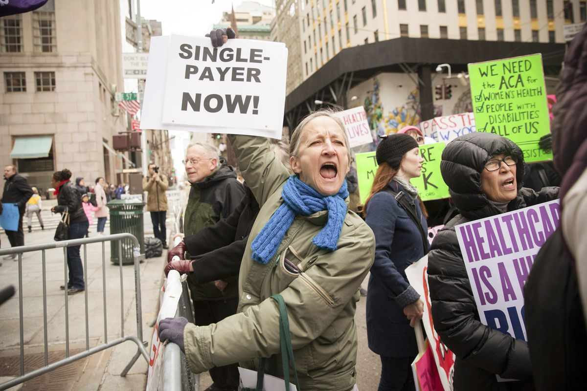 "Health care activist Jean Fox lifts signage promoting the Affordable Care Act during a rally as part of the national ""March for Health"" movement in front of Trump Tower on April 1, 2017 in New York City."