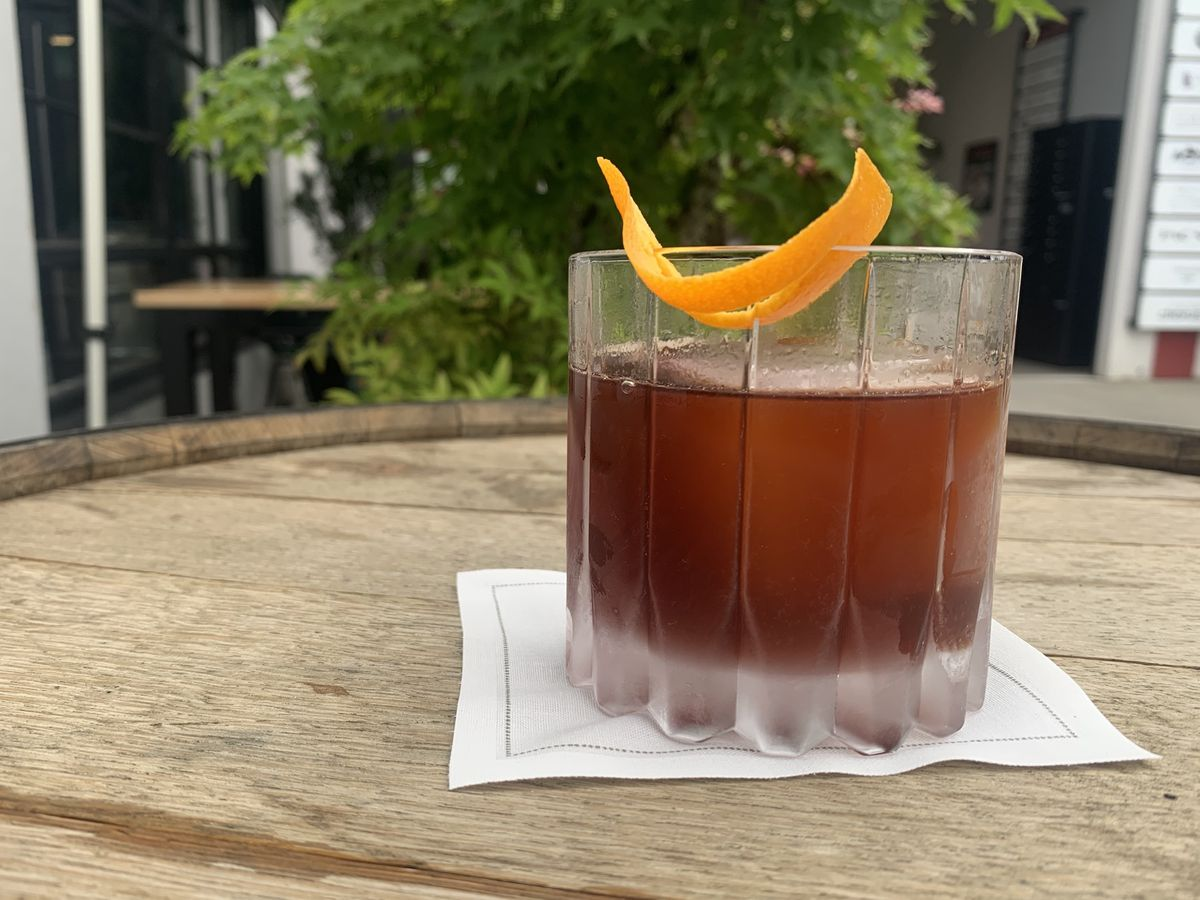 A faceted rocks glass sits atop a white cloth napkin on a wooden barrel. The drink within is dark red, the glass is garnished with an orange peel, and a maple tree is in the background.