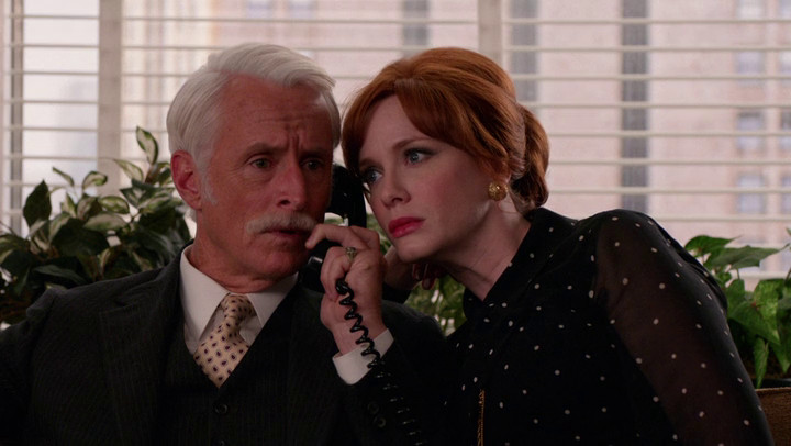 Roger and Joan (Christina Hendricks) listen in on a phone conversation together.