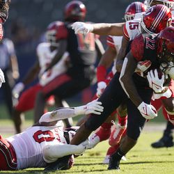 San Diego State running back Greg Bell (22) is tackled by Utah linebacker Devin Lloyd (0) and cornerback Malone Mataele (15) during the first half of an NCAA college football game Saturday, Sept. 18, 2021, in Carson, Calif.