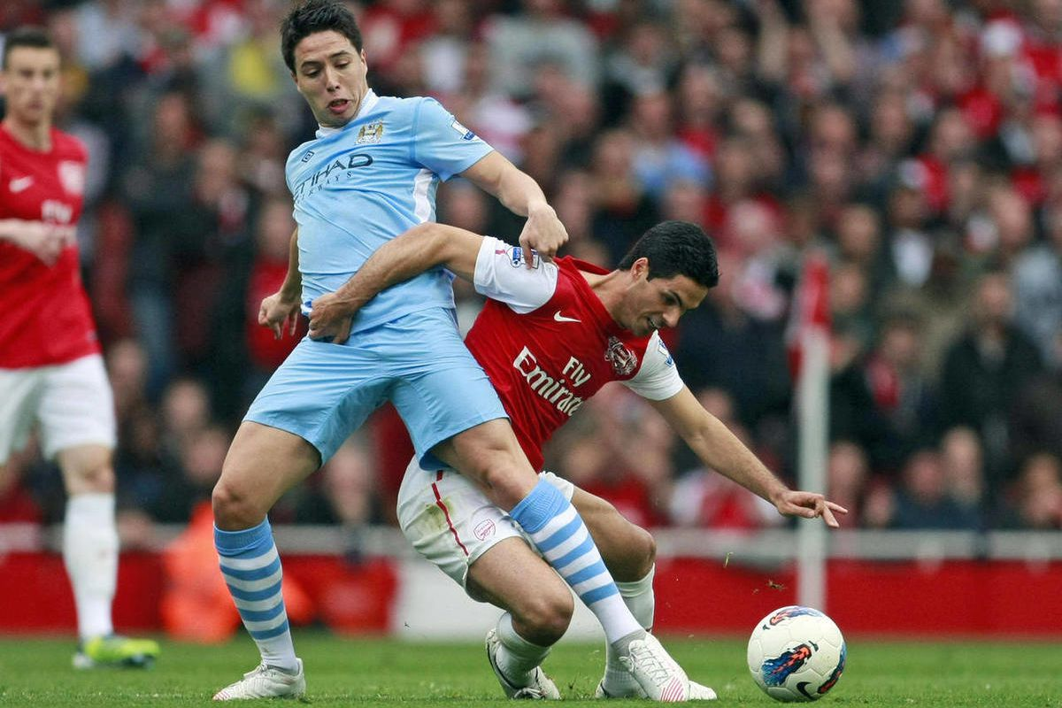 CORRECTS  DAY OF THE WEEK Arsenal's Mikel Arteta, right, is tackled by Manchester City's Samir Nasri during their English Premier League soccer match at the Emirates stadium, London, Sunday, April 8 , 2012.