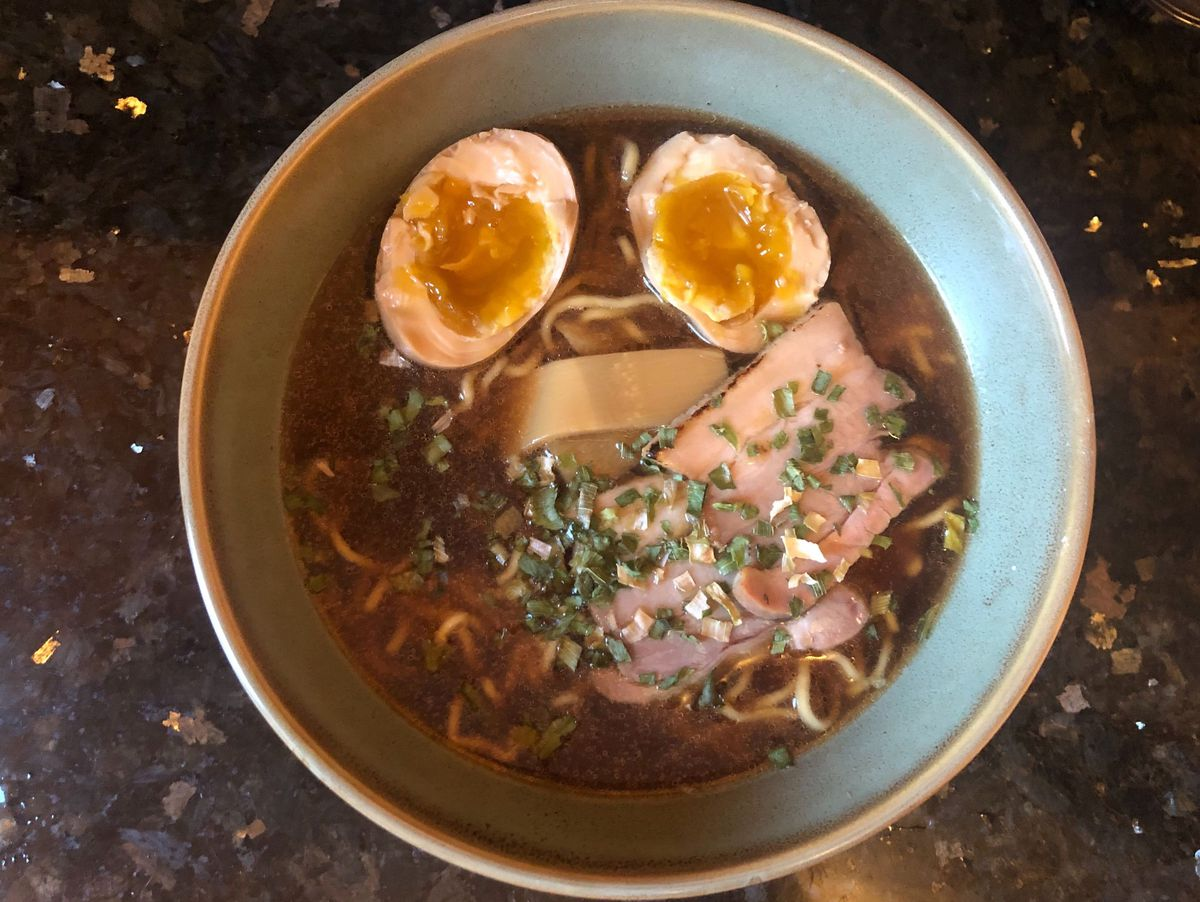 A turquoise bowl filled with brown broth, noodles, and a boiled egg cut in half, set on a dark counter