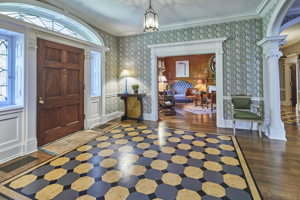 A double-entry foyer features a geometric pattern inlaid into the wood flooring, green patterned wallpaper, and white crown molding trim.