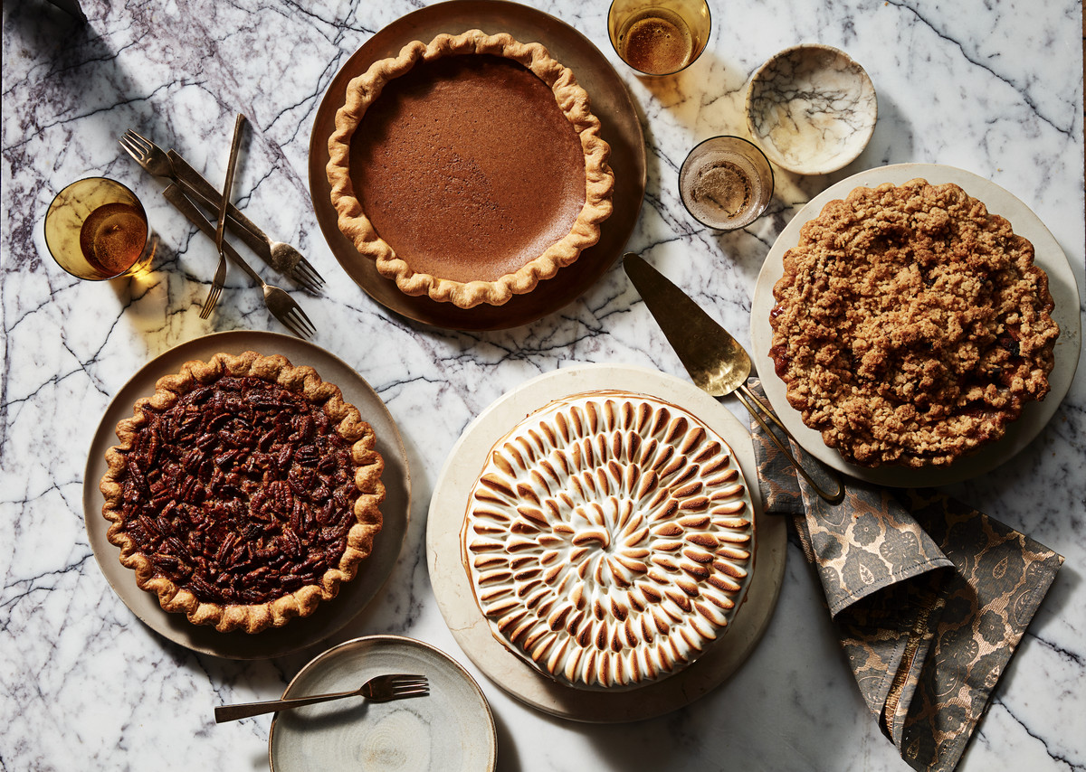A pecan pie, pumpkin pie, a pie with a crumble top, and a pie with marshmallow topping on a marble counter surrounded by utensils and dinnerware.