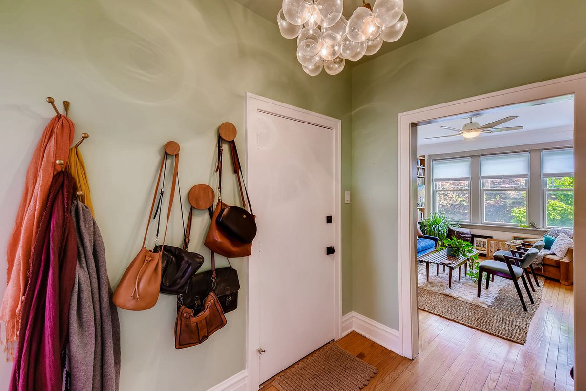 An entryway hooks for scarves and bags next to a white door.