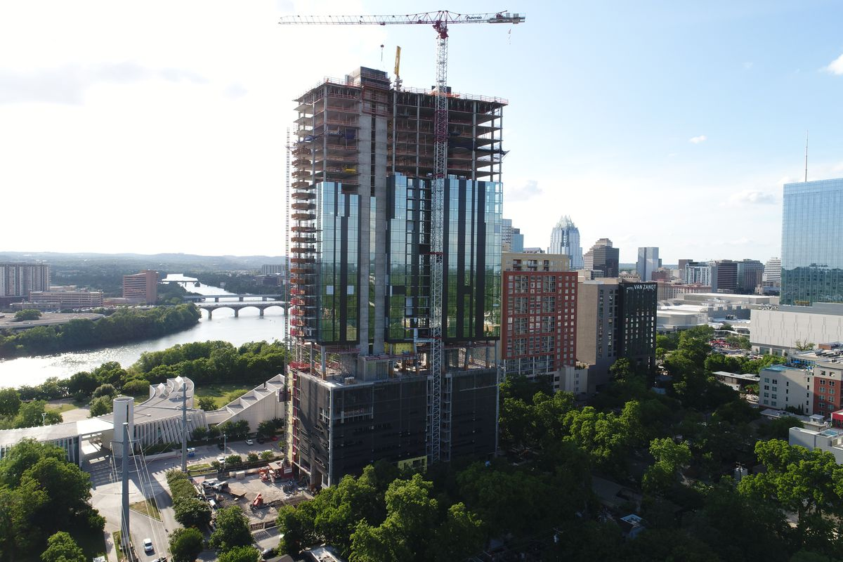 High-rise under construction with a crane over top, Downtown Austin and river behind