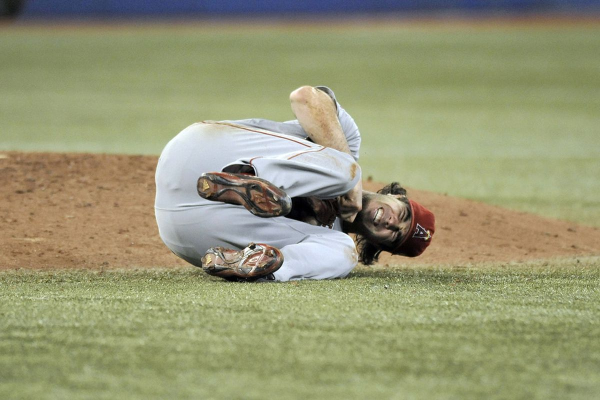 Dan Haren wincing in pain after being hit by an Eric Thames line drive.