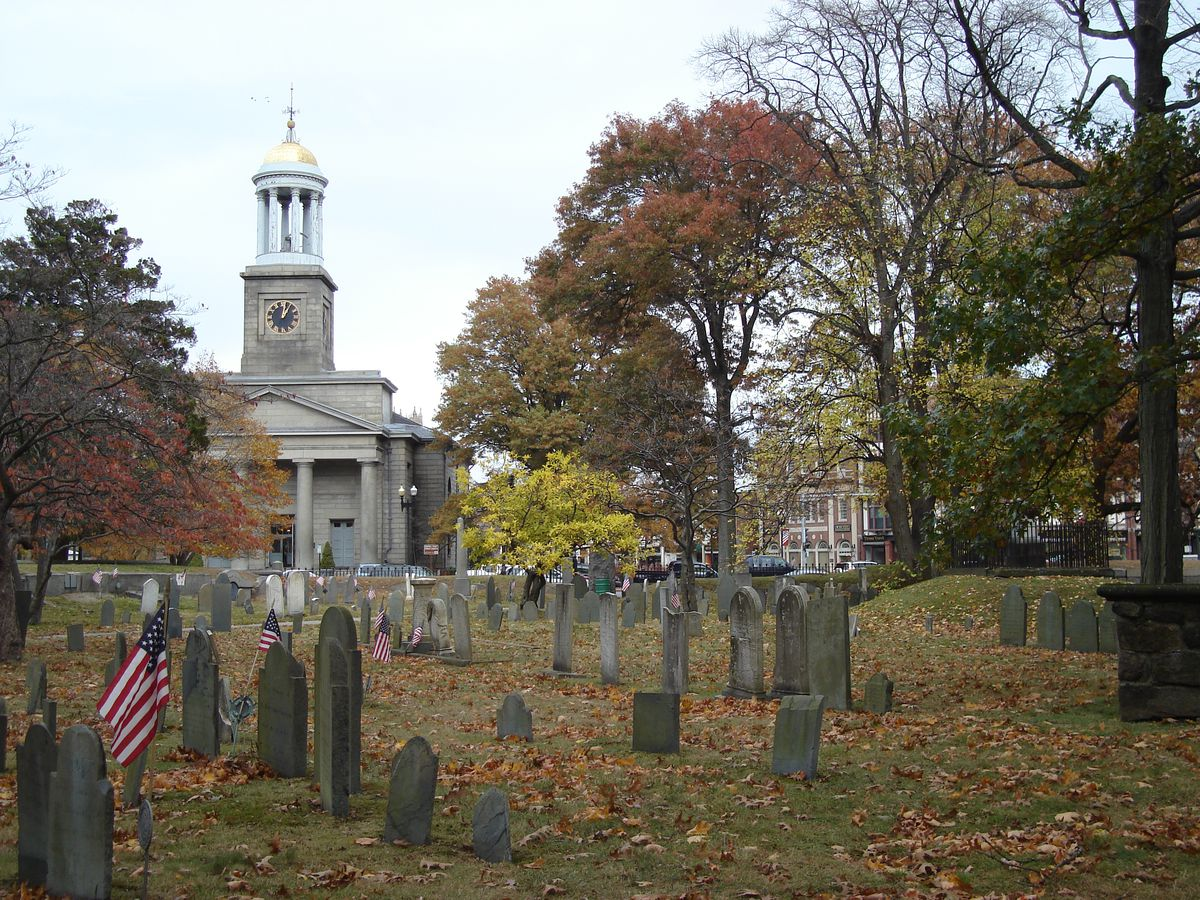 Rows of headstones amid leaf-covered ground, with a church with a spire in the distance.