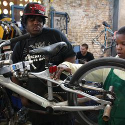"""In this Tuesday, Oct. 11, 2010 photo, Antwane Pritchett, 10, works on a bicycle with the help of Reginald Graham, 15, in Chicago. Graham is a bike mechanic apprentice at the Blackstone Bicycle Works, a bike shop that has an after-school program where young people can earn a free bike by working at the shop for 25 hours. Graham has earned several bikes. Pritchett was working to earn his first bike. Two years ago, Graham put on a bike mechanic""""™s apron for the first time, and something clicked."""