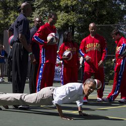 President Barack Obama does pushups during the White House Easter Egg Roll hosted by the president and first lady Michelle Obama, Monday, April 9, 2012, at the White House in Washington.
