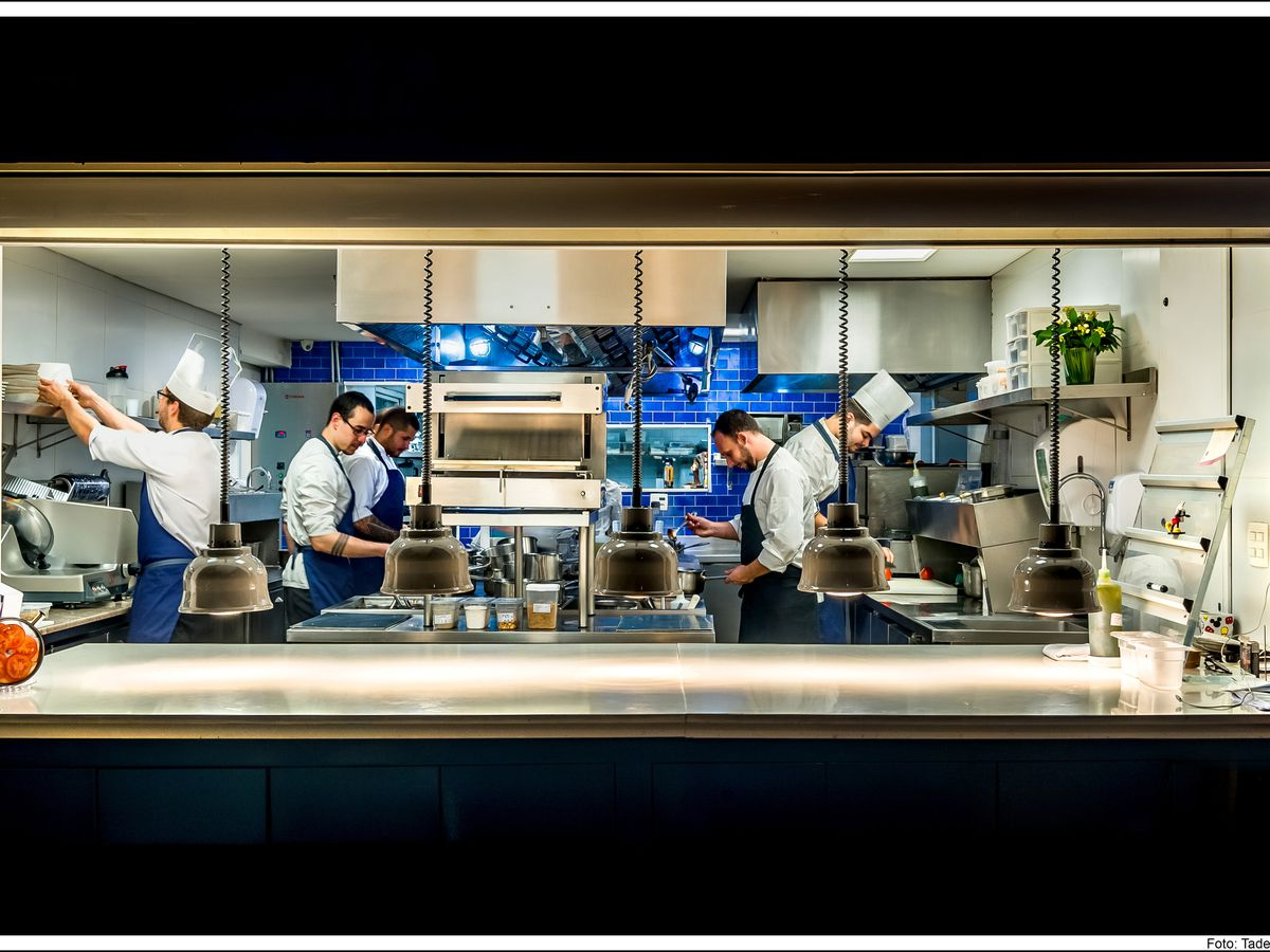 A kitchen team works in an open kitchen, with steel kitchen machines, a bright backsplash, and their uniforms all contrasting colorfully, all seen through the cutout from a dark dining room.
