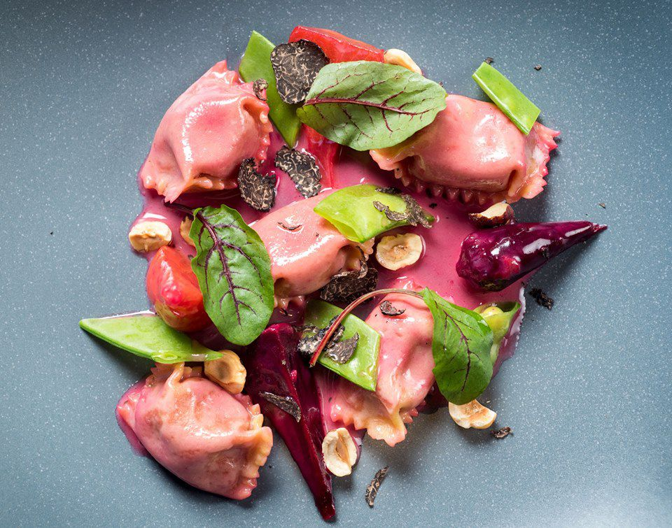 grey plate with pink stuffed pasta, arranged with small green beet leaves