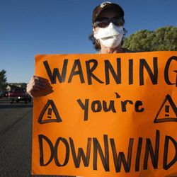 Kathi Murray holds a sign during a rally asking Utah Gov. Gary Herbert to shut down Stericycle's medical waste incinerator in North Salt Lake on Thursday, Sept. 25, 2014.