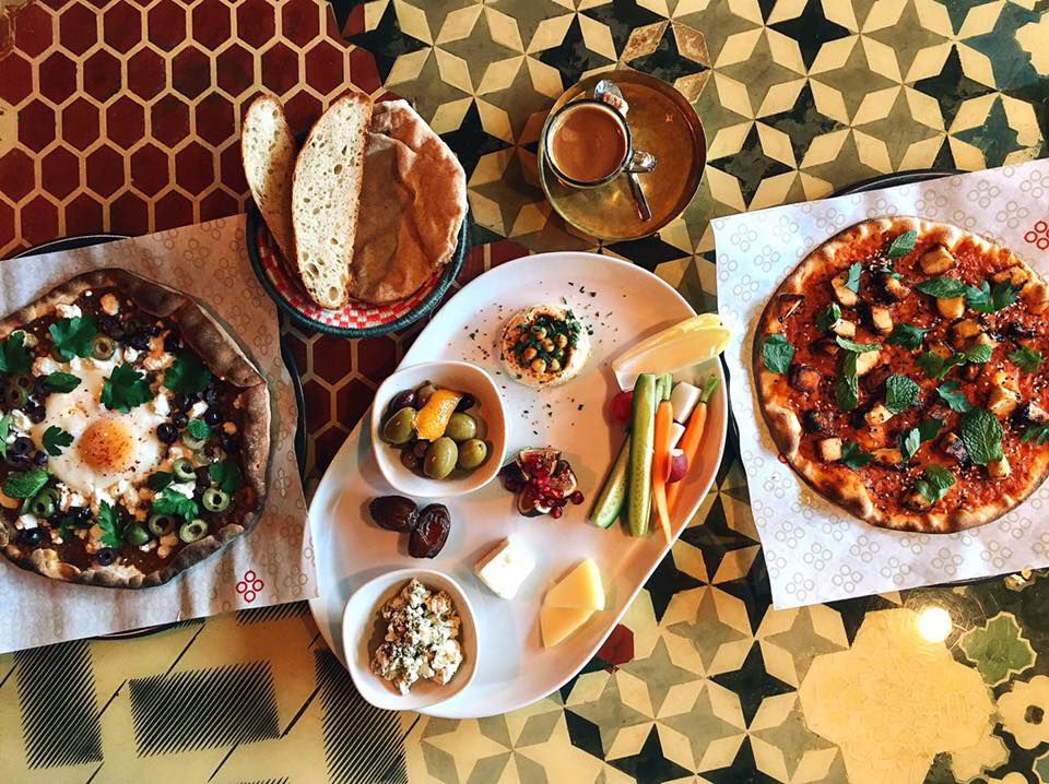 A bird's eye view of colorful pizzas and appetizers at Mamnoon.