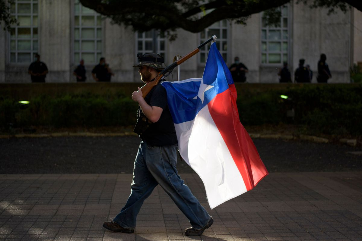 A man walks with a rifle and a Texas flag attached to it during a police appreciation rally in Houston, Texas, on June 18, 2020.