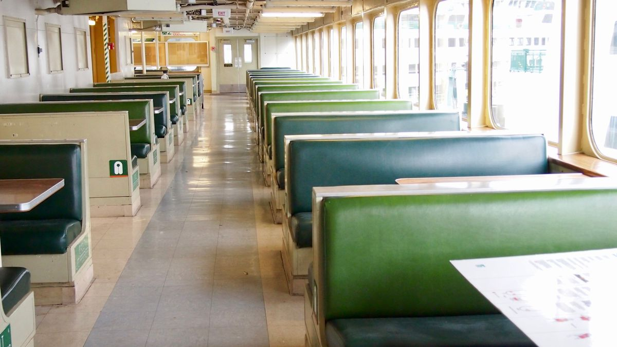 Two rows of green bench seats with tables along a row of windows