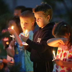 Children hold candles during a vigil held in honor of Sgt. Derek Johnson  in Draper Sunday, Sept. 1, 2013. Johnson was shot and killed this morning.