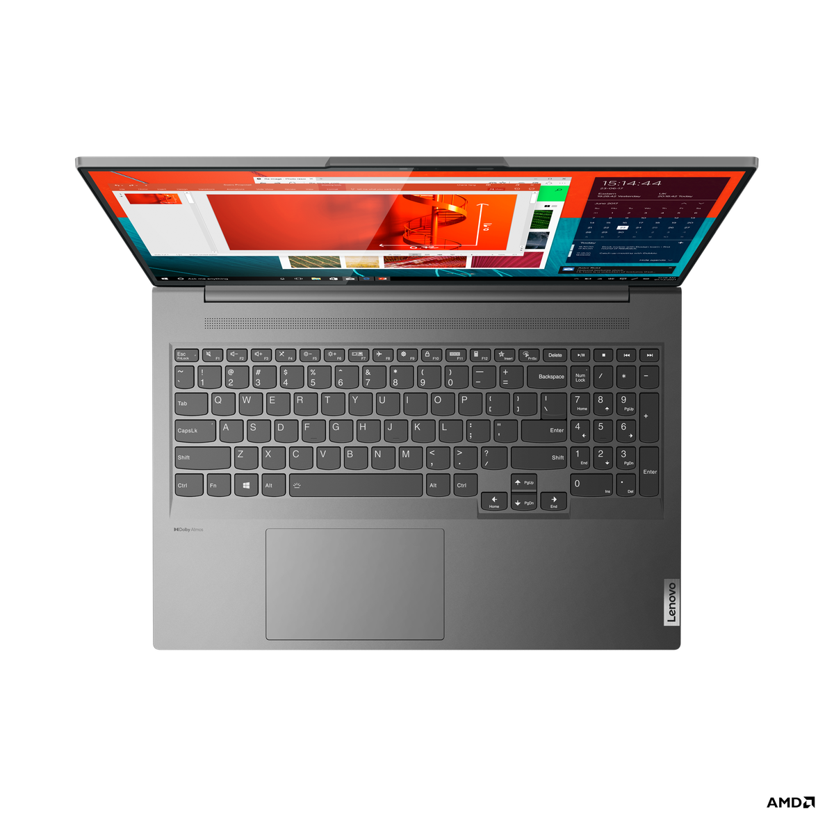 The keyboard of the Lenovo Yoga Slim 7 Pro seen from above on a white background. The screen displays a few windowed apps on an orange background.
