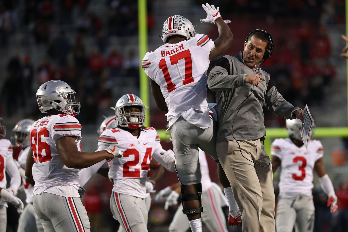 COLLEGE PARK, MD:  Ohio State Buckeyes linebacker Jerome Baker (17) celebrates a Maryland Terrapins turnover with defensive coordinator Greg Schiano at Capital One Field at Maryland Stadium.