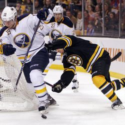 Buffalo Sabres' Cody Hodgson (19) comes around the net as Boston Bruins' Andrew Ference, right, defends in the first period of an NHL hockey game in Boston, April 7, 2012.