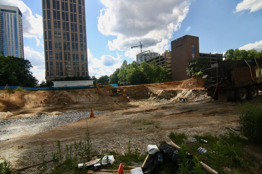 A backhoe and construction truck in a large pit with buildings around.