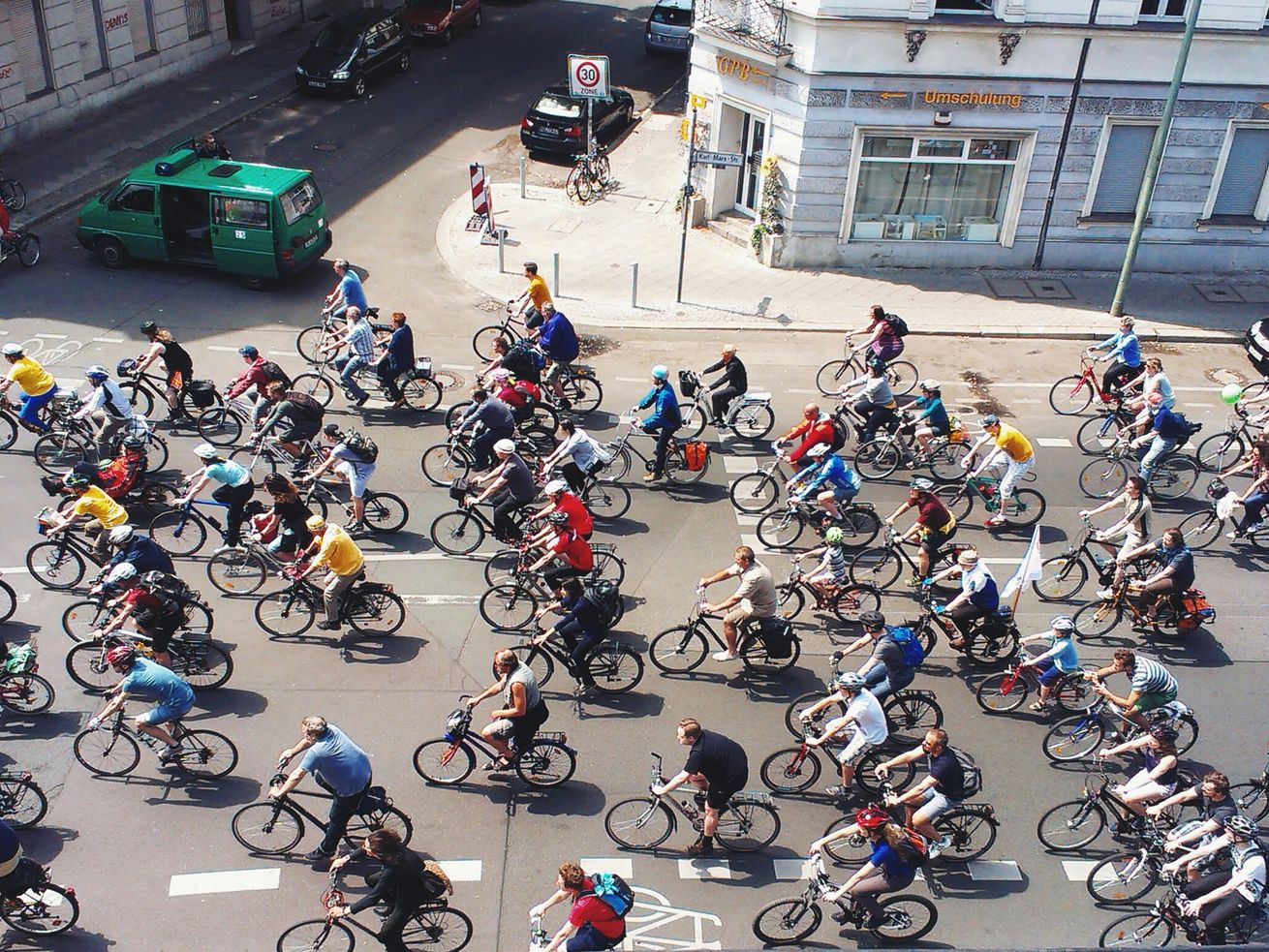 A stream of bikers rides down a city street.