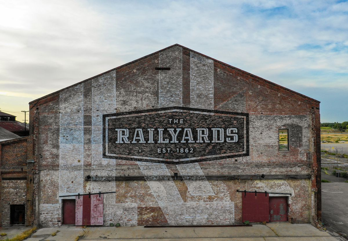 A faded brick building with a new Railyards logo painted on the side.