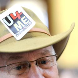 """Jan Bartlett wears his """"U4ME"""" (Utahns for the Medicaid Expansion) sticker on his during a rally in the rotunda at the state Capitol on Wednesday, Nov. 20, 2013, in Salt Lake City. The group rallied to show Gov. Gary Herbert he has support if he decides to expand Medicaid."""