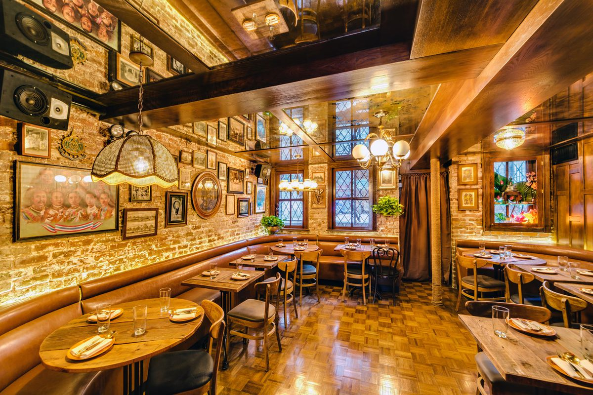 The interior of wood paneled restaurant with lots of photos on the wall and wooden dining tables and chairs