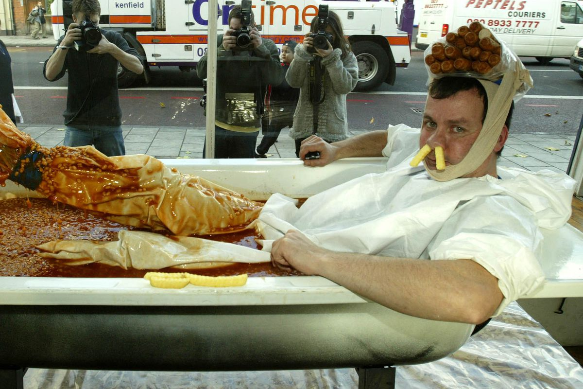 Artist Sits In Bath Of Sausages, Chips And Beans