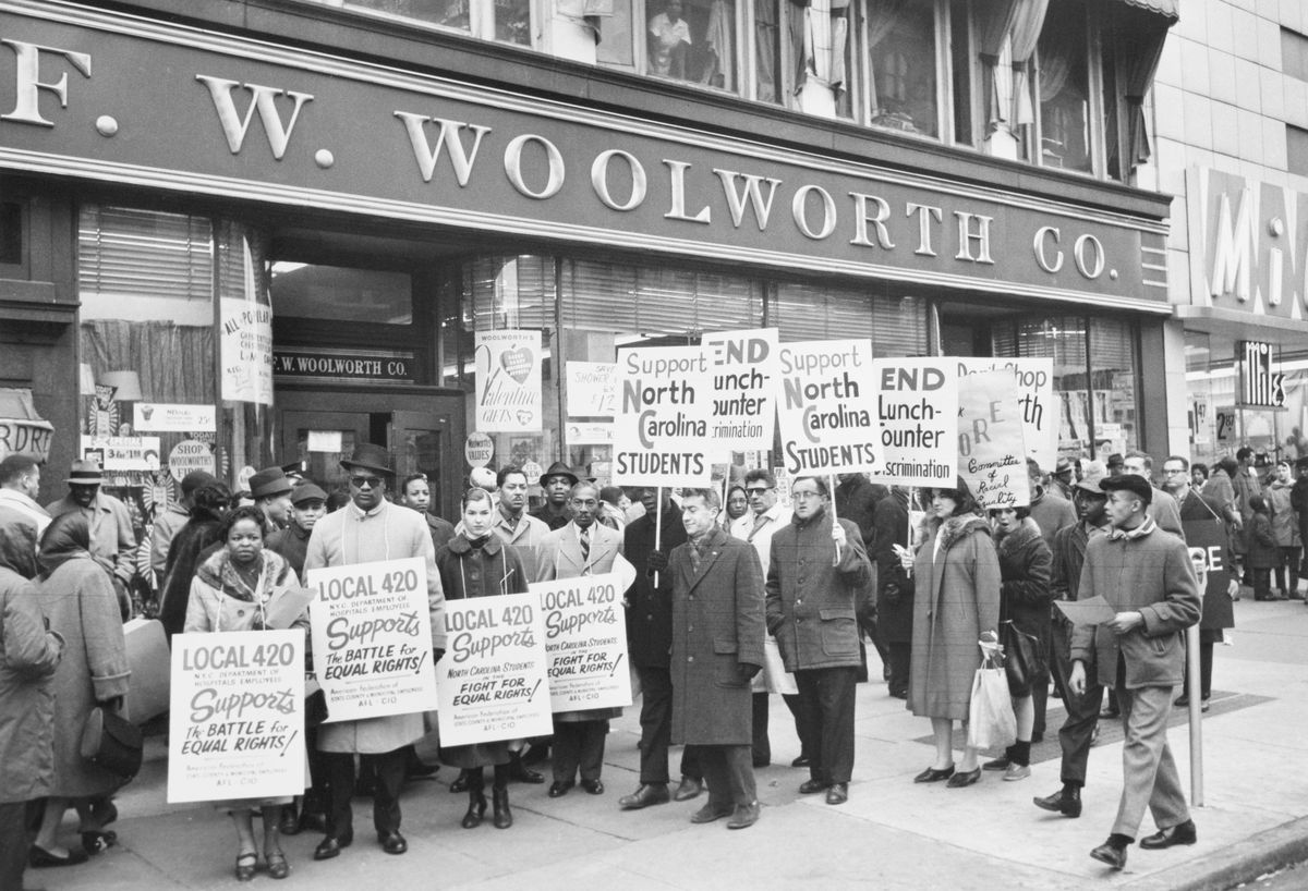 Black and white CORE demonstrators stand outside of the Harlem Woolworth's store with signs to show solidarity with southern protesters in 1960.