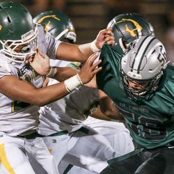 Kearns wide receiver Keeven Wilson (21) blocks Olympus offensive lineman James Sheets (56) during the second half of a high school football game at Olympus High School in Holladay on Friday, Aug. 30, 2019. Kearns won the game 26-21.