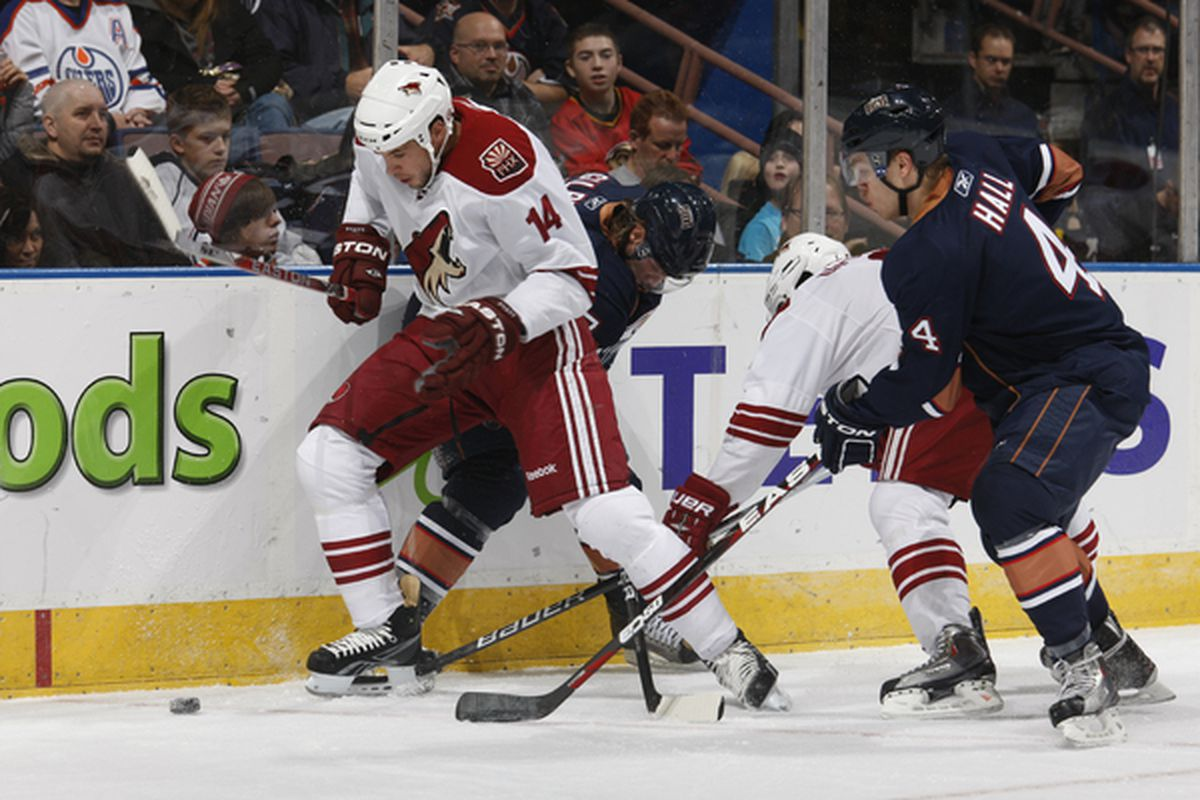 EDMONTON CANADA - NOVEMBER 19: Taylor Pyatt #14 of the Phoenix Coyotes fights off Taylor Hall #4 and Tom Gilbert #77 of the Edmonton Oilers at Rexall Place November 19 2010 in Edmonton Alberta Canada. (Photo by Dale MacMillan/Getty Images)