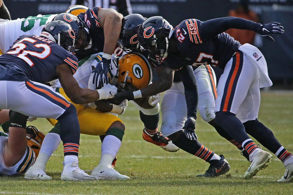 Jamaal Williams of the Green Bay Packers is gang-tackled by Kahlil Mack, Akiem Hicks #96, Roquan Smith and Sherrick McManis of the Chicago Bears at Soldier Field on December 16, 2018 in Chicago, Illinois.