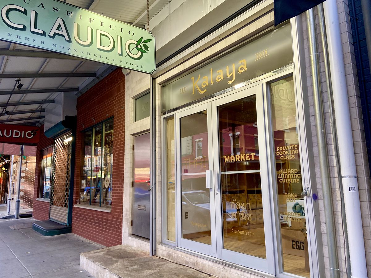 glass-front and red brick stores next to each other with signs that says kalaya and claudio
