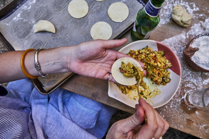 A woman fills mini empanadas