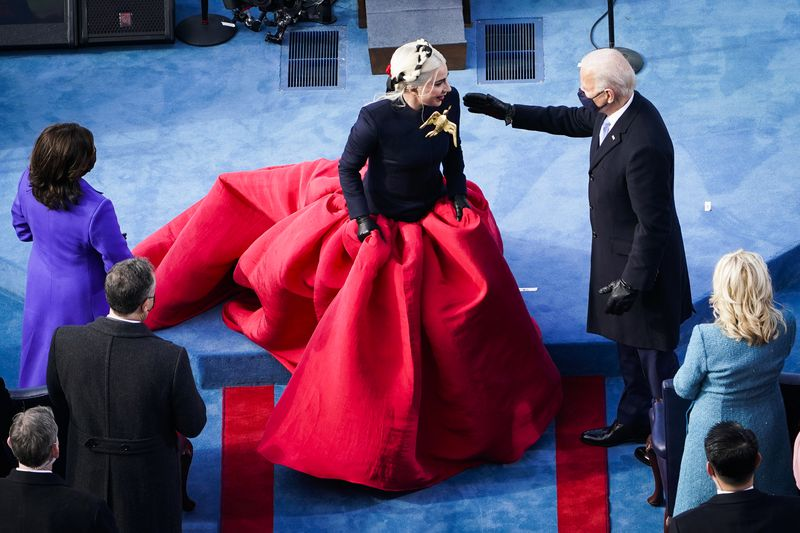 Lady Gaga in a large flowing red dress being greeted by President Biden.