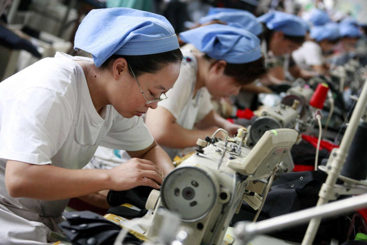 Female Chinese workers sew clothes to be exported to southeast Asian countries at the garment factory of Huaibei Qiuyan Industrial And Trading Co., Ltd. in Huaibei city, east Chinas Anhui province, 1 October 2011.