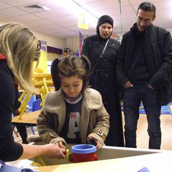 Kindergarten teacher Susan Cody, left, shows newly arrived Syrian refugee Dania Khatib, 5, around a classroom as her mother Mahasen Boshnaq, center rear, and father Ahmed Khatib, right, watch at the Northwest Primary School, Friday, Jan. 27, 2017, in Rutland, Vt. The parents fled Syria in 2012 and the family lived in Turkey until they arrived in Rutland earlier this month.