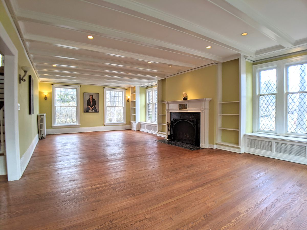 A long and empty room with hardwood floors. The walls are painted a light yellow with white-painted wood trim.