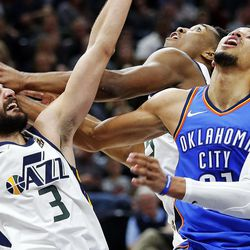 Utah Jazz guard Ricky Rubio (3), Utah guard Donovan Mitchell (45) and Oklahoma City Thunder guard Andre Roberson (21) fight for a rebound during NBA basketball in Salt Lake City on Saturday, Dec. 23, 2017.