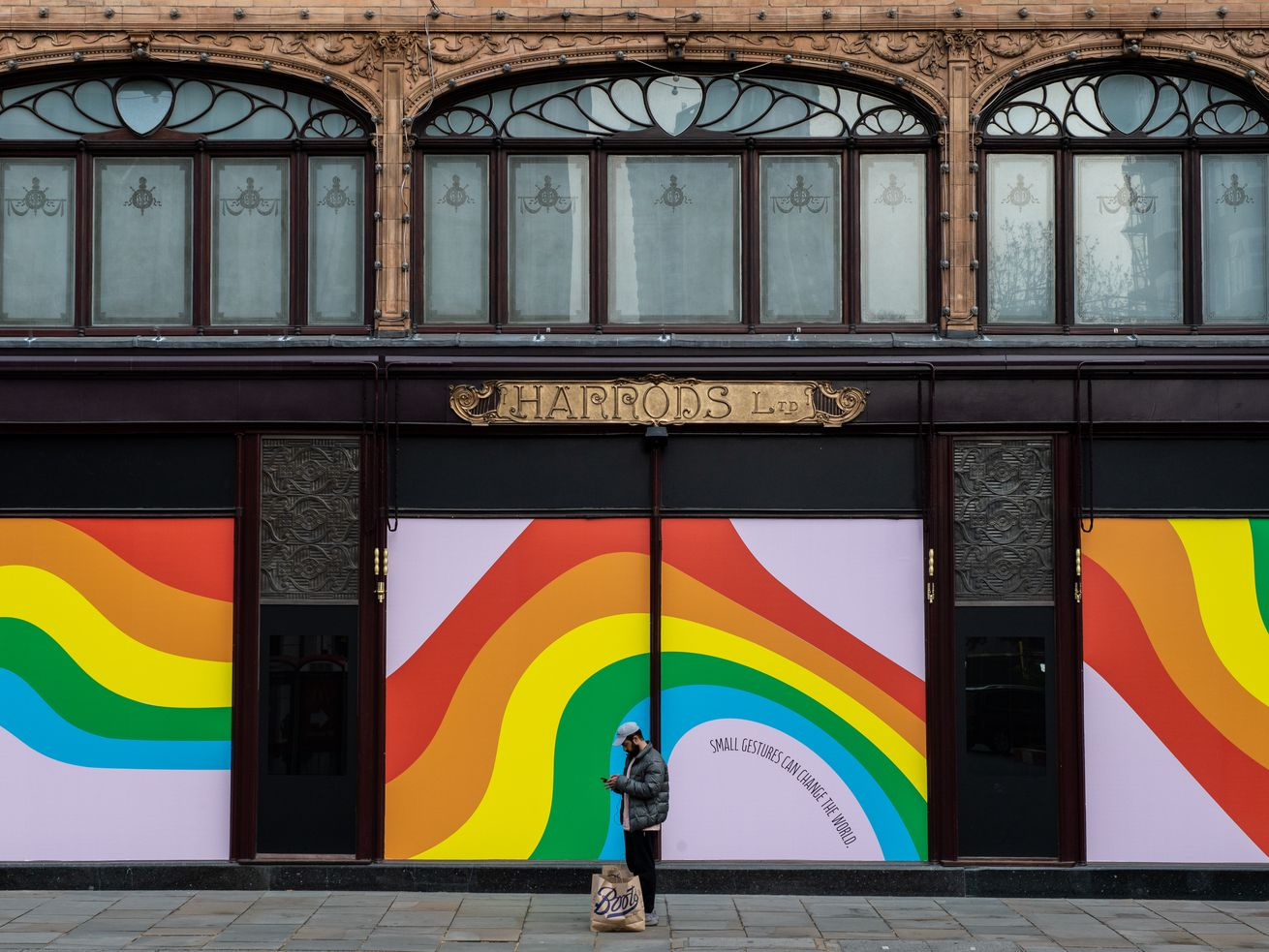 A man looks at his phone while standing outside boarded-up windows at Harrods London department store.